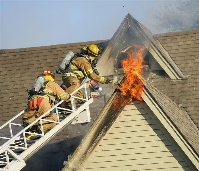 Two firemen on ladder fighting second story flames