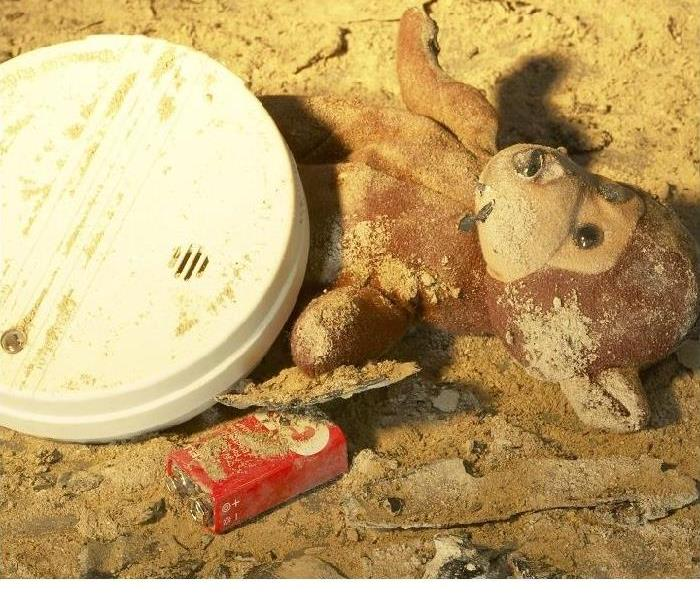 Smoke detector, battery, and stuffed animal covered in ash after a fire