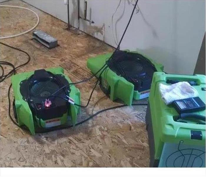 A Dehumidifier and air mover working  to remove the last vestiges of water vapor in floor