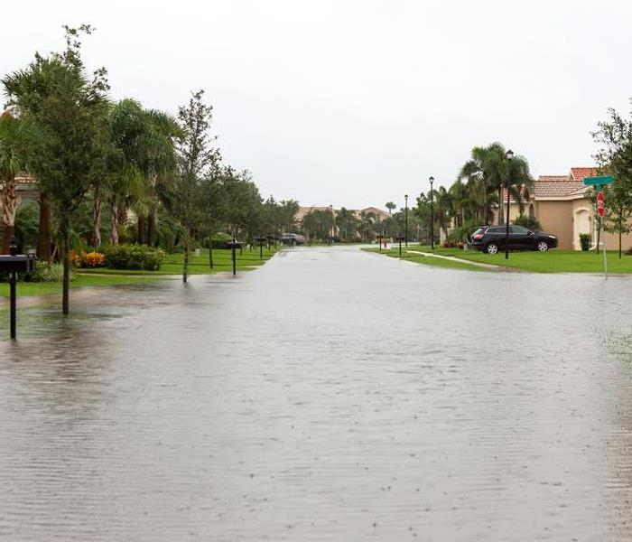 A street in a neighborhood with standing water.
